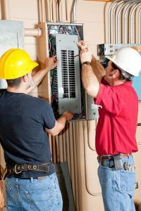 two electricians in hard hats working on electrical panel