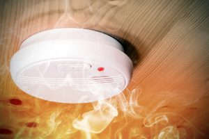 Common plastic white home smoke detector alarm, preventing an abnormal smoke in the room from perhaps a fire with a sound very loud. In the image, there is a big fire in the room and there is smoke that rises to the ceiling where is placed the equipement. This one is mounted on wooden ceiling. For example in France country, those smoke detector are required since march 2015. On the sensor is written that we should not paint it, and direction to open or close it, there is the test button because we need to check it regularly, and a red led indicating that the battery inside is always good.