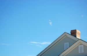 roof of older home on blue sky background
