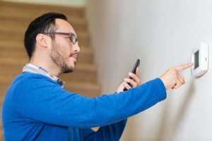 man looking at smart phone while he sets thermostat